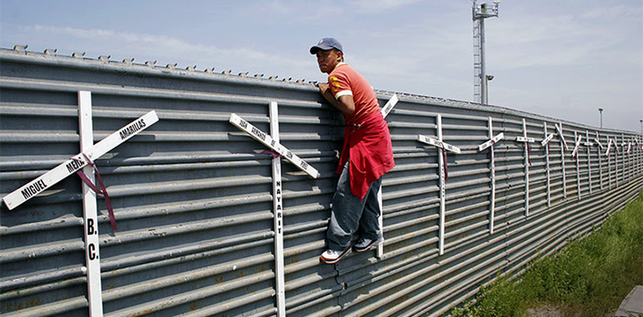 A migrant attempts to cross the US-Mexico border fence. Source: Wikimedia
