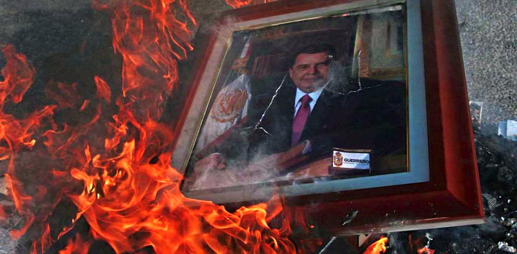 Protesters burn the portrait of Guerrero Governor Angel Aguirre in front of the government palace in Chilpancingo.